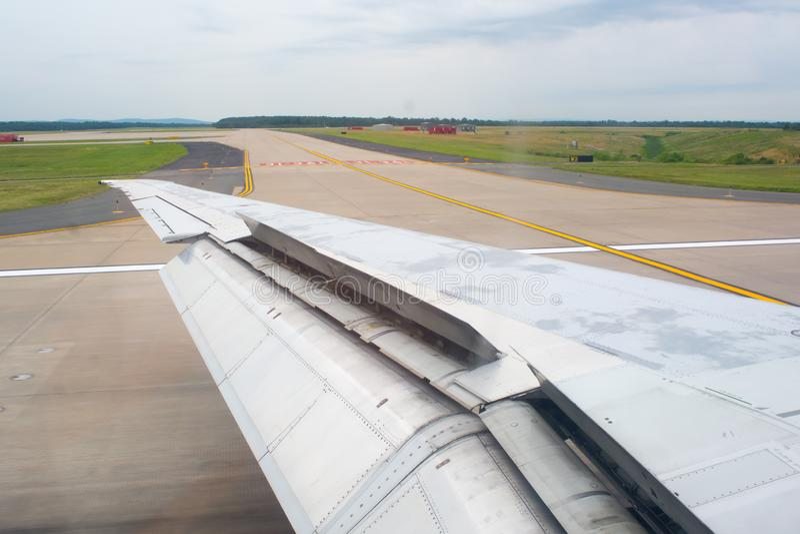 Stäng sig upp av en vinge av ett flygplan med klaffar upp under åka taxi på landningsbanan royaltyfria foton
