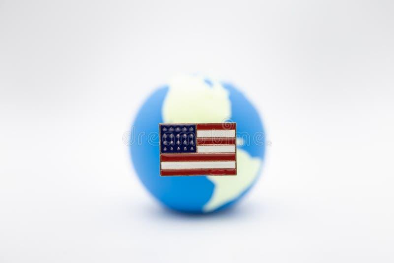 Stäng sig upp av enigt tillstånd av den Amerika stiftnationsflaggan över mini- världsboll på vit bakgrund arkivfoton