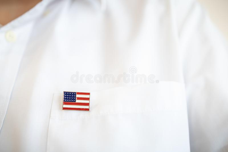 Stäng sig upp av enigt tillstånd av den Amerika stiftnationsflaggan på det vita skjortafacket arkivbilder