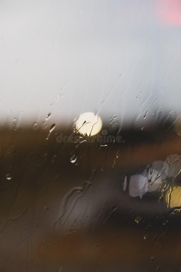 Stäng sig upp av ett exponeringsglas med gjorda suddig regndroppar och ljus arkivfoton