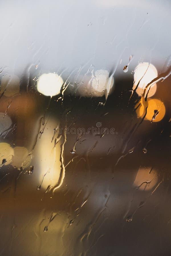 Stäng sig upp av ett exponeringsglas med gjorda suddig regndroppar och ljus royaltyfri bild