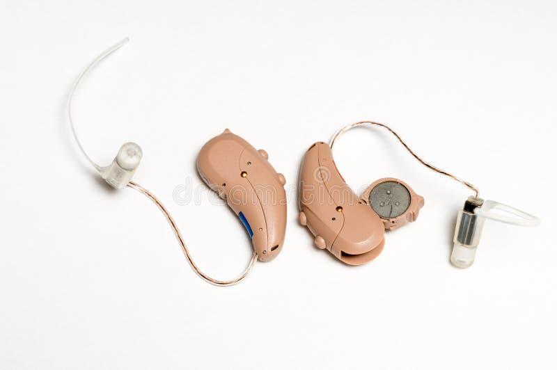 Stäng sig upp av ett par av mycket små moderna hörapparater på vit bakgrund royaltyfri fotografi