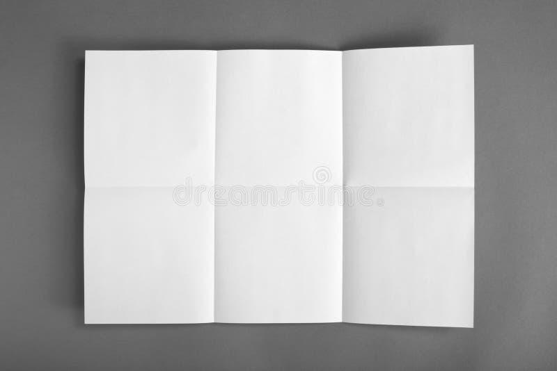 Stäng sig upp av ett skrynkligt uppvecklat stycke av papper på grå backgroun arkivbilder