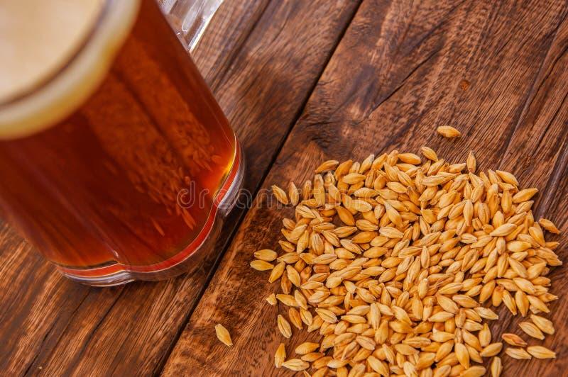 Stäng sig upp av exponeringsglas av öl med vete i grunden på en trätabell royaltyfria foton