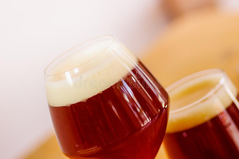 Stäng sig upp av exponeringsglas av mörkt öl med skum på en trätabell royaltyfri foto