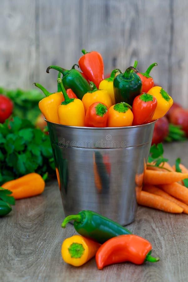 Stäng sig upp av färgrika mini- söta peppar i en tappningkorg royaltyfri bild