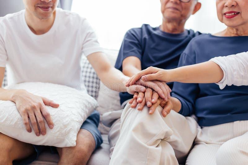 Stäng sig upp av familjen med vuxna barn och pensionärföräldrar som sätter händer som tillsammans hemma sitter på soffan tillsamm arkivfoto