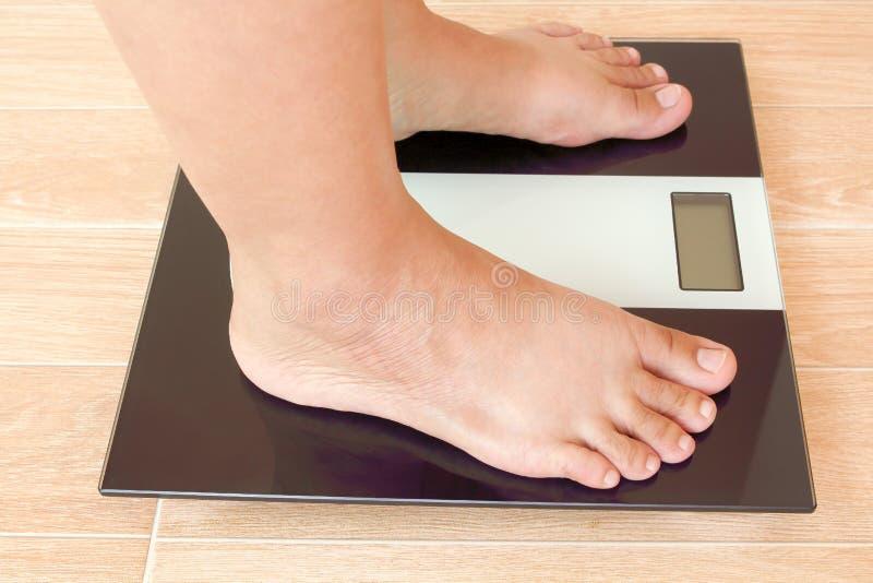 Stäng sig upp av fet kvinnlig fot som står på viktskala royaltyfria bilder
