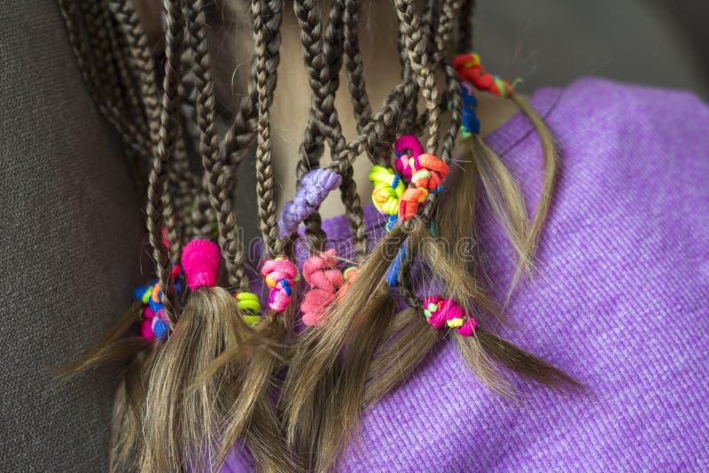 Stäng sig upp av flätad trådhår av lilla flickan med färgrika gummiband royaltyfri fotografi