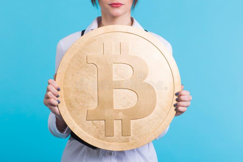 Stäng sig upp av flickan som rymmer guld- bitcoin och att blinka och att tänka om crypto valuta arkivfoto