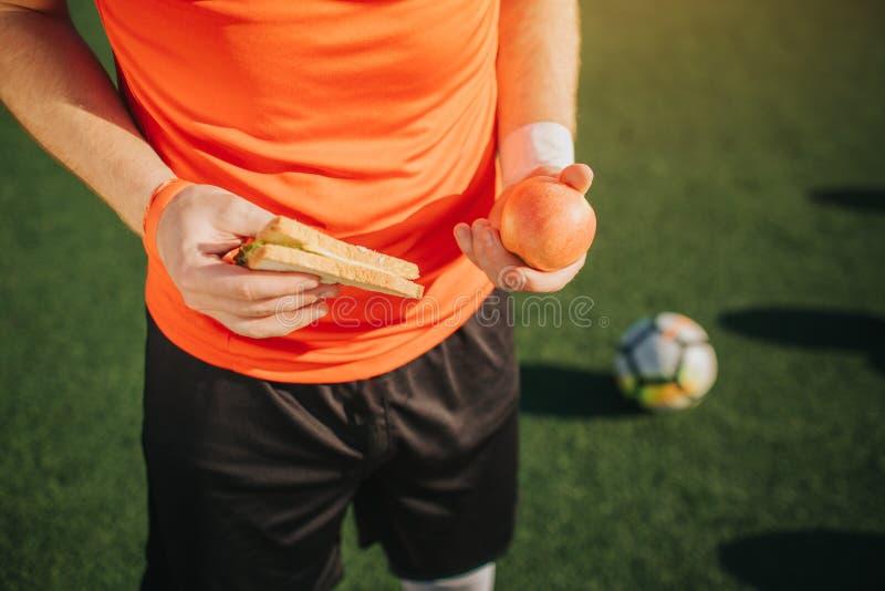 Stäng sig upp av fotbollplaueer som rymmer äpplet och smörgåsen i händer Han står bara Boll som ligger på grön gräsmatta förutom  royaltyfri bild