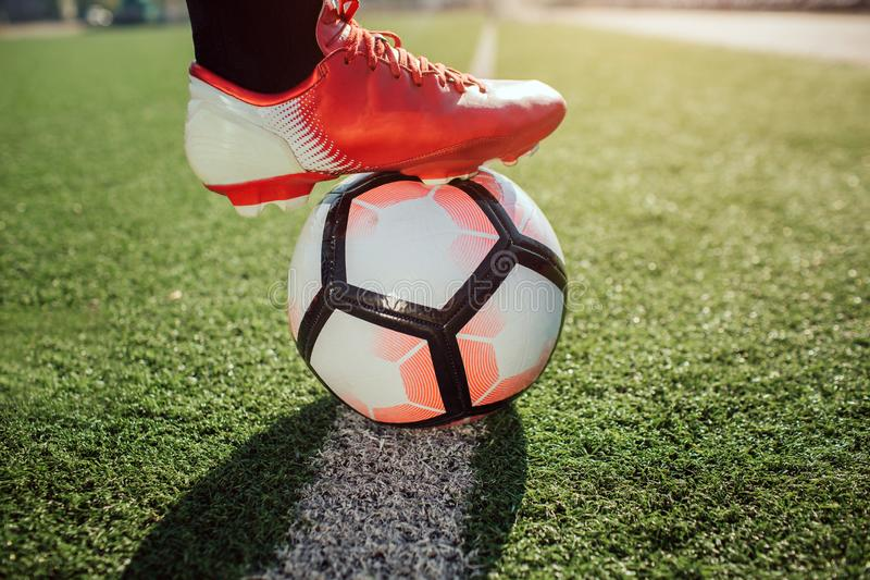 Stäng sig upp av fotbollsspelarefot i sockergymnastikskor Han rymmer det på boll Bollställning på den vita linjen som målas på gr royaltyfri foto