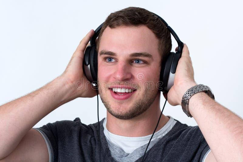 Stäng sig upp av framsidan av den unga mannen som lyssnar till musik royaltyfri fotografi