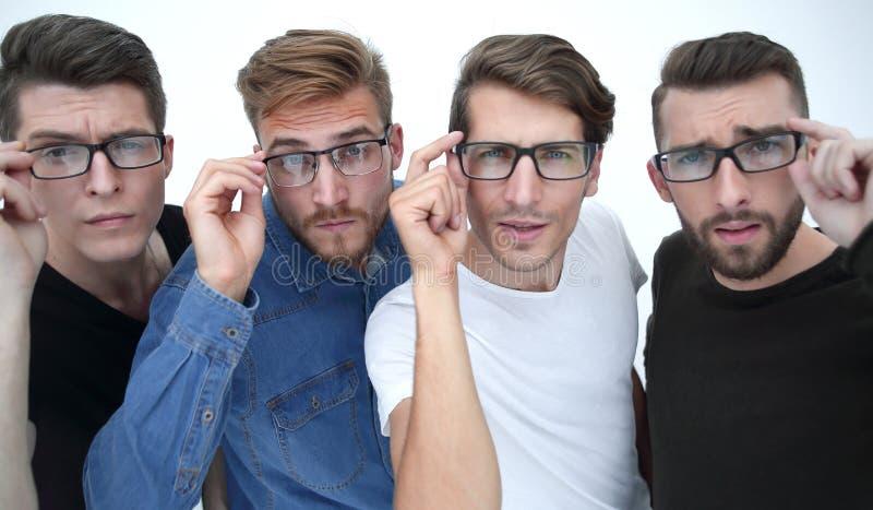 Stäng sig upp av fyra lyckliga kollegor som arbetar i exponeringsglas arkivfoto