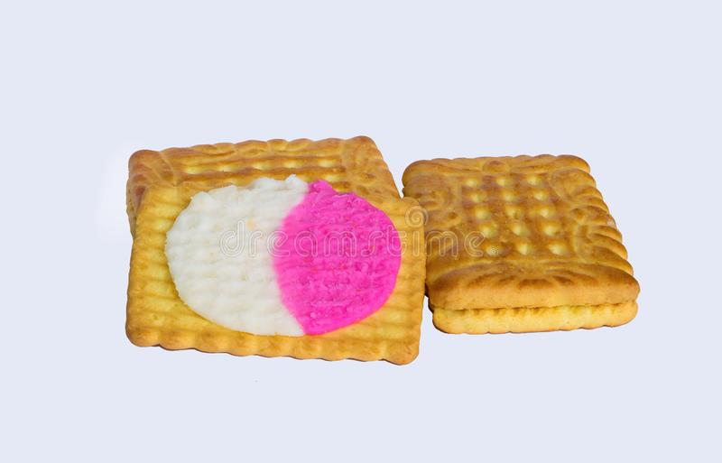 Stäng sig upp av fyrkantiga formkex som fylls med vit och rosa kräm som isoleras på en vit bakgrund royaltyfri bild