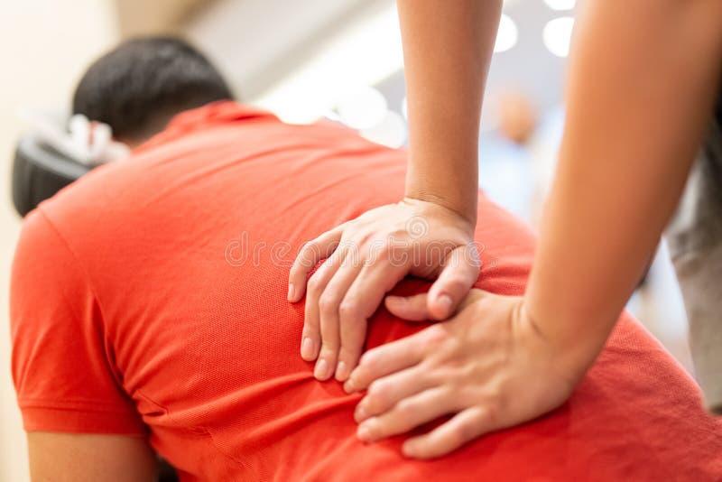 Stäng sig upp av fysioterapeuten som ger massage till en patient arkivfoton