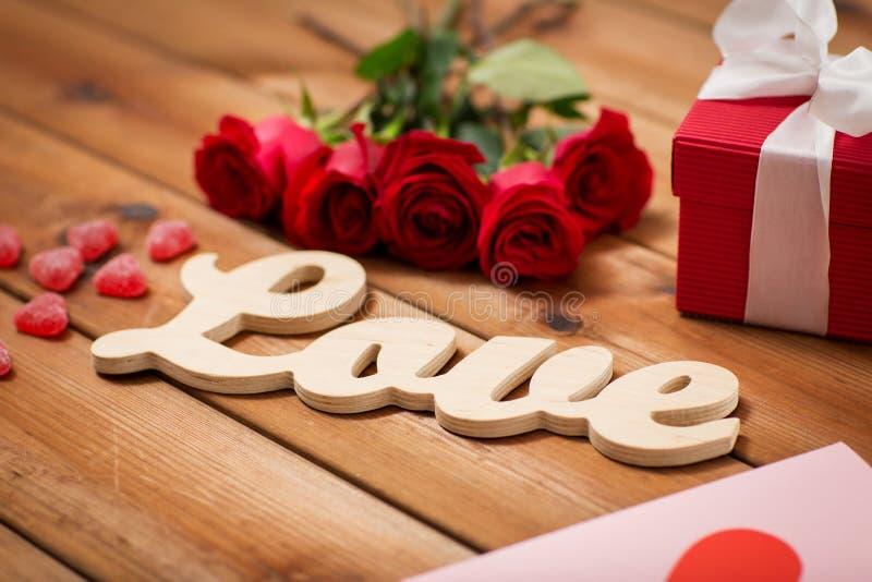 Stäng sig upp av gåvaasken, röda rosor och hälsningkort fotografering för bildbyråer