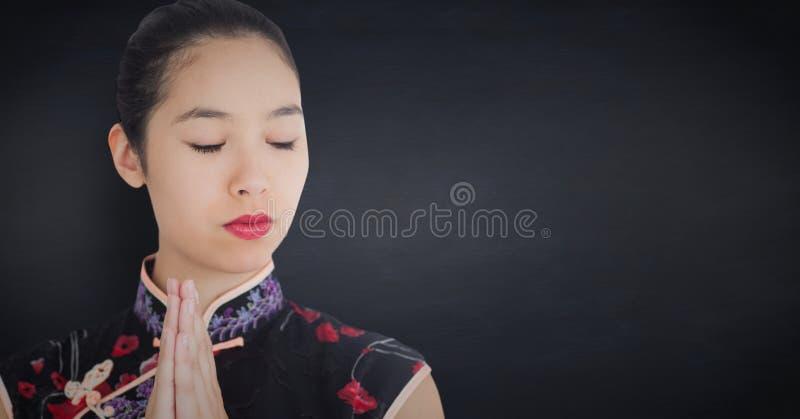 Stäng sig upp av geisha med händer tillsammans mot den svart tavlan för marinen arkivbilder