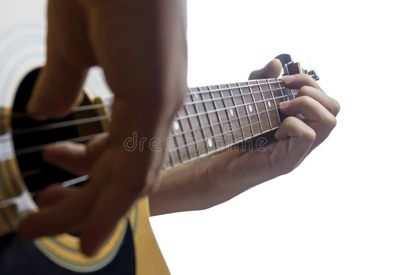 Stäng sig upp av gitarristhanden på den klassiska gitarren arkivfoto