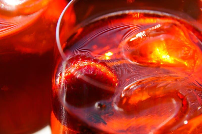 Stäng sig upp av glaskanten av den röda coctailen med jordgubbe- och iskuber royaltyfri bild