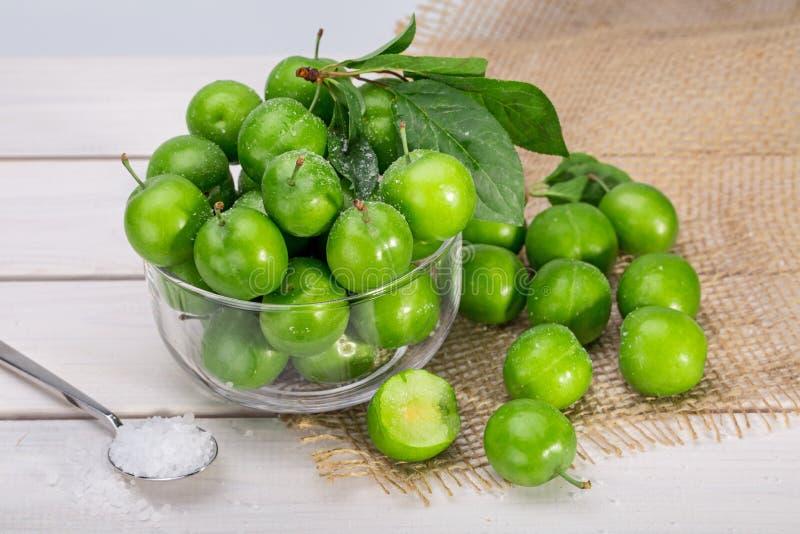 Stäng sig upp av gröna plommoner eller renklon i en glass bunke och en sprinkl arkivfoton