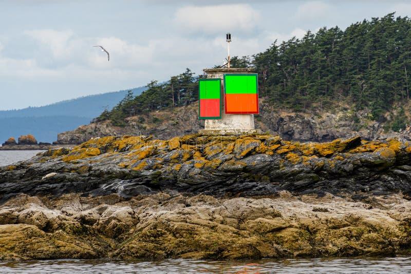 Stäng sig upp av grönt, och den orange navigeringmarkören på vaggar i det Salish havet, den forested ön och den molniga himlen i  arkivbild