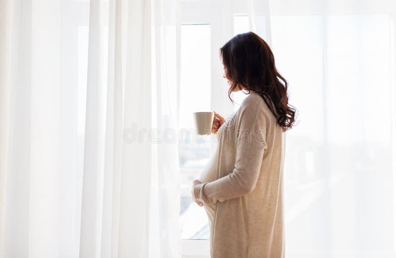 Stäng sig upp av gravid kvinna med tekoppen på fönstret royaltyfria bilder