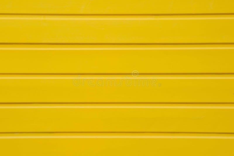 Stäng sig upp av gul träpanelbakgrundstextur arkivfoton