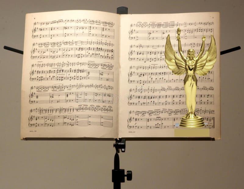 Stäng sig upp av guld- trofé- och musikanmärkningsställning royaltyfria bilder