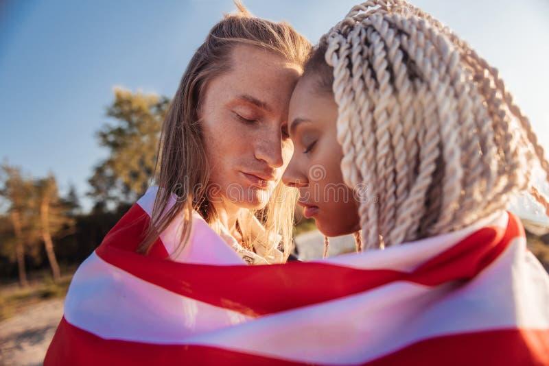 Stäng sig upp av gulliga snygga par som reser samman med nationsflaggan arkivfoto