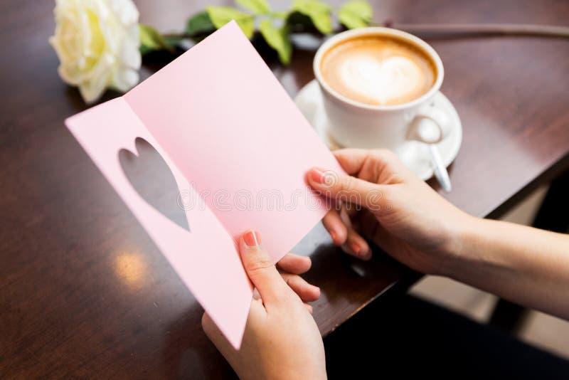Stäng sig upp av hälsningkort och kaffe för kvinna läs- arkivfoton