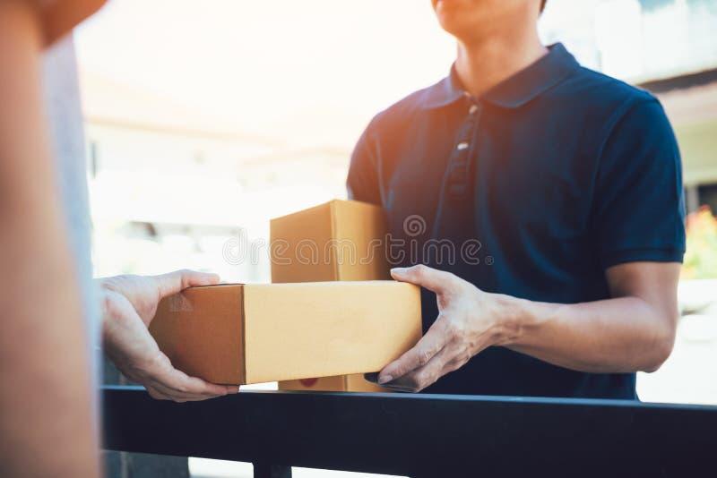 Stäng sig upp av händer, last sompersonalen levererar kartonger med jordlotter inom till mottagarens hand fotografering för bildbyråer