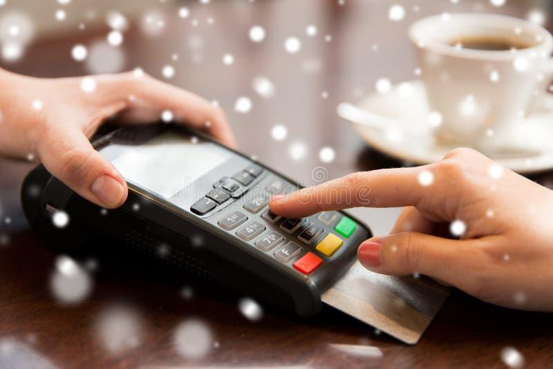 Stäng sig upp av händer med kreditkortavläsaren på kafét arkivbild