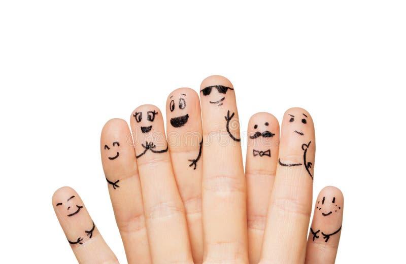 Stäng sig upp av händer och fingrar med smileyframsidor royaltyfria bilder