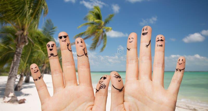 Stäng sig upp av händer och fingrar med smileyframsidor arkivbilder