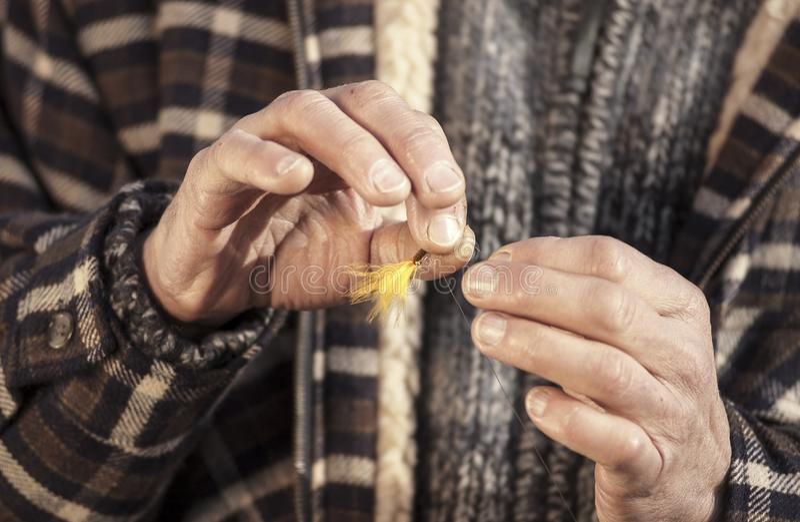 Stäng sig upp av händer som binder fiska flugan royaltyfri fotografi