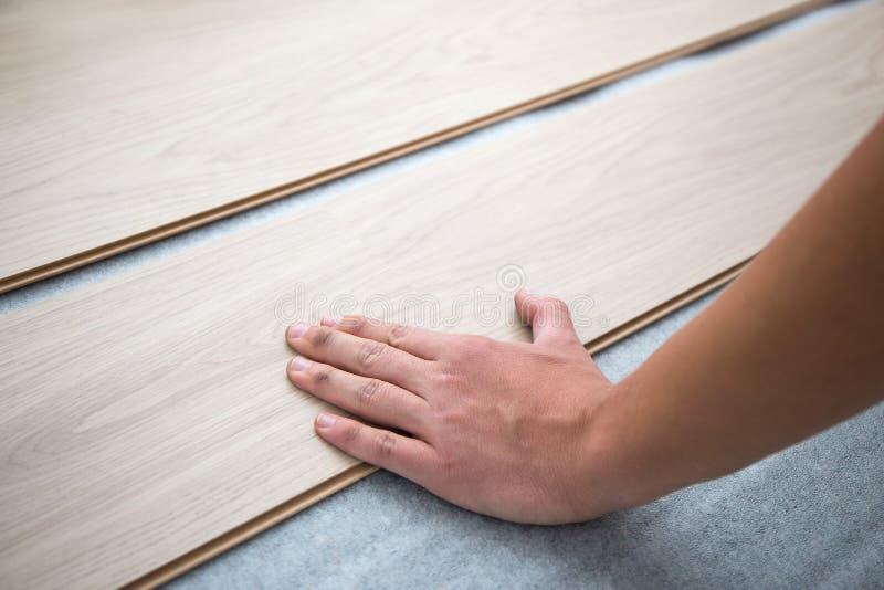 Stäng sig upp av händer som installerar det nya pläterade trägolvet royaltyfri bild