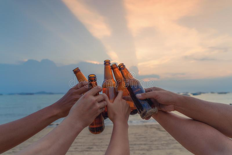 St?ng sig upp av h?nder av v?nner som tillsammans klingar flaskor av ?l och firar p? ferie i parti p? stranden eller havet i somm royaltyfri fotografi