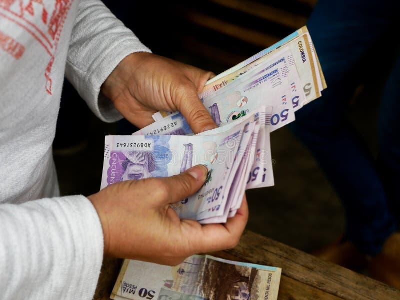 Stäng sig upp av händerna av en kvinna som räknar femtio colombianska pesos för tousand arkivbilder