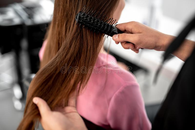 Stäng sig upp av händerna som trycker på långt hår och använder hårborsten fotografering för bildbyråer