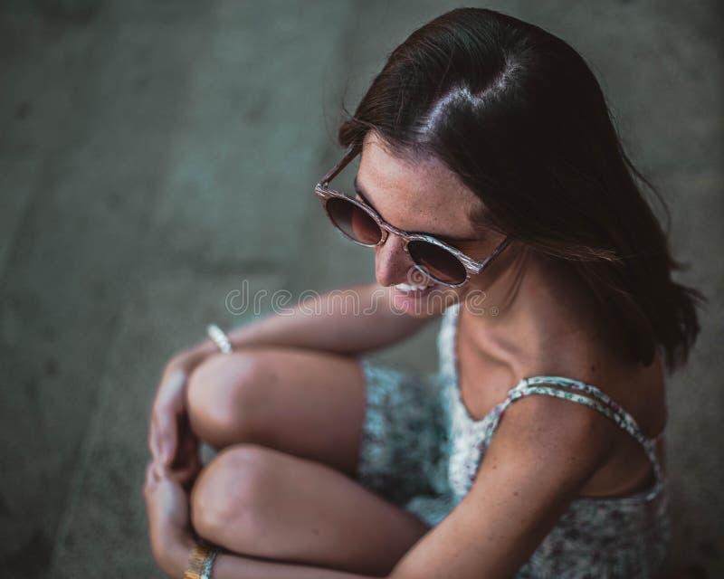 Stäng sig upp av härlig brunettflicka i solglasögon som sitter på trappa Henne som bort ser och ler royaltyfri fotografi