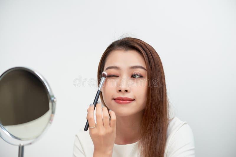 Stäng sig upp av härlig framsida av den asiatiska unga kvinnan som får smink arkivfoto