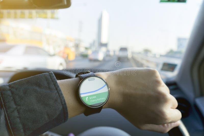 Stäng sig upp av hållande ögonen på smartwatch för man och användaapplikationen Google Maps arkivfoton