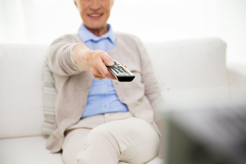 Stäng sig upp av hållande ögonen på tv för den lyckliga höga kvinnan hemma arkivfoto