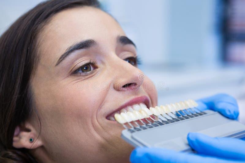 Stäng sig upp av hållande utrustning för tandläkare, medan undersöka kvinnan på kliniken royaltyfri fotografi