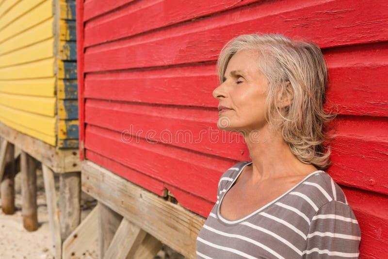 Stäng sig upp av hög kvinna med ögon stängt anseende vid väggen royaltyfria foton