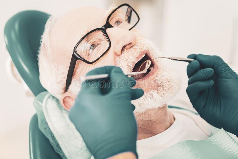 Stäng sig upp av hög patient i tand- stol royaltyfria bilder