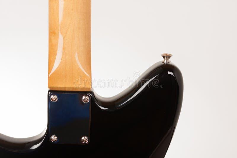 St?ng sig upp av halsplattan p? den svarta elektriska gitarren med bulten p? hals, den bakre sikten, studiofors royaltyfri fotografi