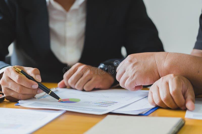 Stäng sig upp av handen för affärsmannen som arbetar med finansiell information om affärsgraf och att analysera investeringdiagra arkivfoto