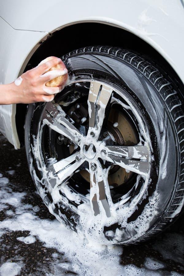 Stäng sig upp av handen med hjulet för svamptvagningbilen royaltyfri foto